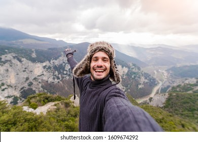 Happy and smiling hiker taking a selfie on the top of the mountain raising arm up. Portrait of an handsome man on a nature background