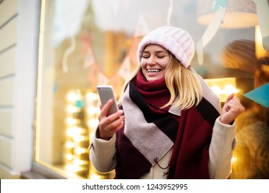 Happy smiling hipster girl received good news in text message on mobile phone while standing outdoors near shop window with burning lights. Cheerful lucky woman reading e-mail on cellphone