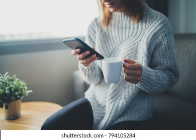 Happy smiling hipster girl using smartphone device while chilling at home wearing cozy knitted sweater, attractive young woman chatting with friends at social network while sitting on sofa at home