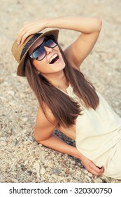 Happy smiling hipster woman in hat on a sea beach