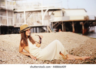 Happy smiling hipster woman take a rest lying on a sea beach, casual dress and hat