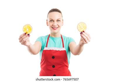 Happy smiling hypermarket supermarket seller showing orange slices wearing red apron isolated on white background
