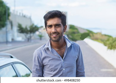 Happy smiling indian male outdoor next to his car