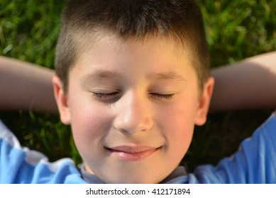Happy smiling joyful beautiful boy having fun outdoor and lying on green grass. Family summer sunny holiday (vacations) concept