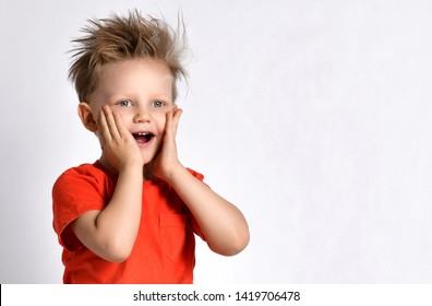 Happy smiling kid boy in orange t-shirt with his hands on his face looks at something amazing on white background with free text copy space