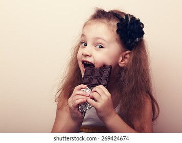 Happy smiling kid girl biting tasty chocolate with empty copy space. Vintage portrait