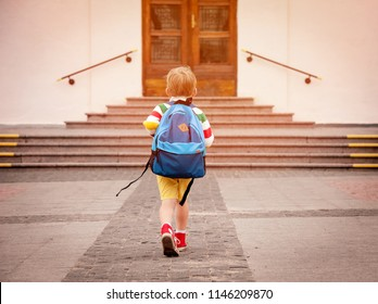 Photo of Happy smiling kid in glasses is going to school for the first time. Child boy with bag go to elementary school. Child of primary school. Pupil go study with backpack. Back to school