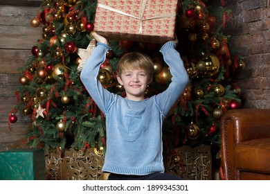 A happy smiling kid holds a Christmas present. The child holds a box in festive packaging. The boy rejoices in the holiday, Christmas, New Year. The boy stands against the backdrop of a Christmas tree
