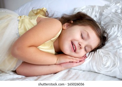 Happy smiling kid sleeping and smiling in her sleep. Dream the little princess on a white bed close-up.