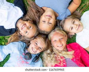 Happy smiling kids looking at the camera on the grass, topview