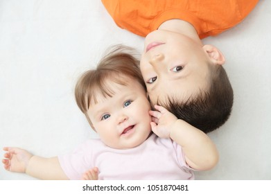 happy smiling kids, portrait of boy and baby girl looking at each other, happiness in childhood of siblings, two children lying, boy having small sister
