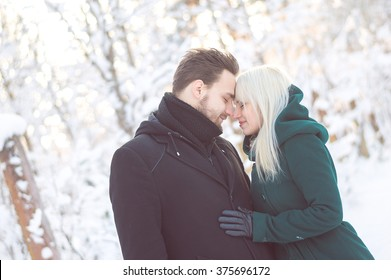 Happy smiling kissing touching couple on walk at winter sunny day