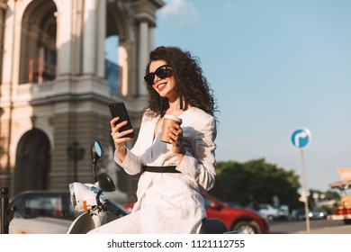 Happy smiling lady with dark curly hair in sunglasses and white costume sitting on white moped with cup of coffee to go and cellphone in hand with city view on background