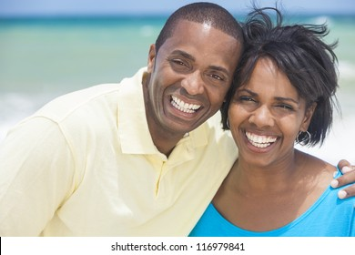 A happy smiling laughing African American man and woman couple at the beach in the summer