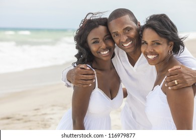 A happy smiling laughing African American family of father mother & daughter at the beach in the summer