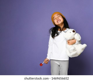 Happy smiling laughing asian girl kid in colorful hat holds polar bear toy and lollipop on blue mint background with free text space. International day of polar bear concept.