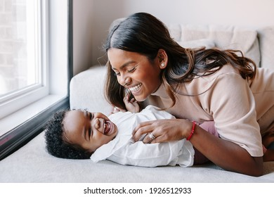 Happy smiling laughing Indian mother playing with black baby girl daughter. Family mixed race people mom and kid together hugging at home. Authentic candid lifestyle with infant kid child.