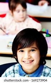 Happy smiling little boy in classroom
