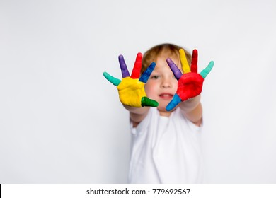 Happy smiling little boy with colored hands on a white background, young artist, white t shirt model