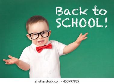Happy smiling little boy on a chalkboard background