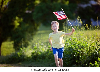 happy smiling little boy running with american flag, celebrating 4th of july