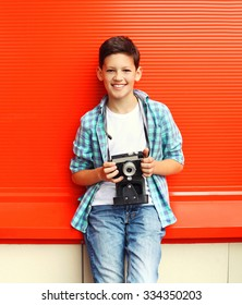 Happy smiling little boy teenager with retro vintage camera in city over red background