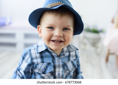 Happy smiling little child boy in a blue hat