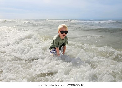 A happy and smiling little child is laughing as he splashes in the ocean waves on a summer day at the beach.