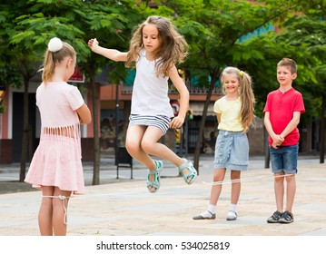 happy smiling little friends in elementary school age playing with chinese jumping rope at playground