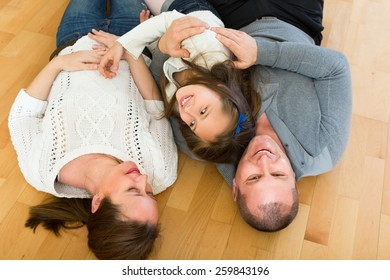 Happy smiling little girl with cheerful parents posing at floor at home