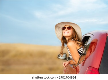 Happy smiling little girl child goes to summer travel trip in the red car. Preteen in hat and sunglasses enjoying road trip.