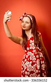 Happy smiling little girl child making self portrait on smartphone