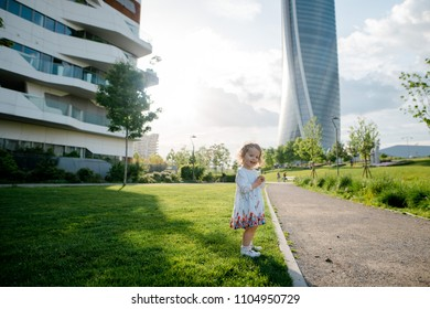 Happy smiling little girl with curly blonde hair in beautiful white dress standing on the green lawn in the city park near the skycrapers. Sunny day