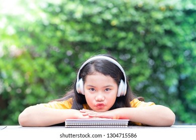 Happy smiling little girl making pucker up face and listening to music in the park with her headphones and resting her chin on colorful notebooks