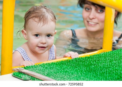 happy smiling little girl with mother at water pool