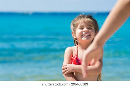 Happy smiling little girl playing at sea, tropical sea background.