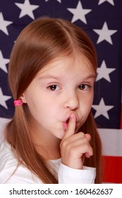 Happy smiling little girl put her finger to her lips as a sign of silence on the background of a large U.S. flag