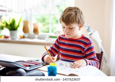 Happy lächelnden kleinen Jungen zu Hause machen Hausaufgaben am Morgen bevor die Schule beginnt. Kleines Kind, das Sport treibt, drinnen. Grundschule und Bildung: Geometrische Boy-Zeichnungen