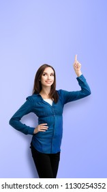 Happy smiling looking up young woman in casual smart blue clothing, showing something or copyspace for text or slogan, over violet background