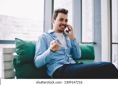 Happy smiling male calling to friend for communicating and discussing time for meeting using 4g wireless internet connection for making smartphone conversation indoors during leisure on cozy couch