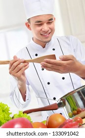 happy smiling male chef taste his cooking in the kitchen