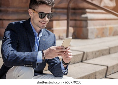 Happy smiling male person typing on phone
