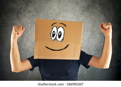 Happy smiling man with cardboard box on his head and raised fists for victory