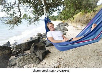 happy smiling man in hammock relaxing on the beach.