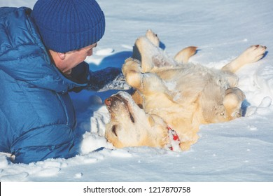 A happy smiling man with a Labrador retriever dog lying in snow in winter. The dog lying on back