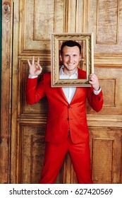 Happy smiling man in a red suit, looking through an empty classic frame.