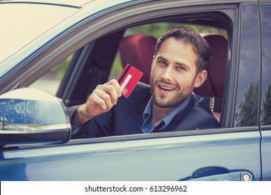 Happy smiling man sitting inside his new car showing credit card. Personal transportation auto purchase concept