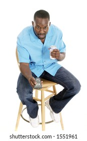 Happy smiling man sitting on a stool holding a remote control aimed forward and holding a can of his favorite beverage.
