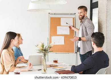 Happy smiling man is standing near board and presenting information to colleagues. People are sitting around table