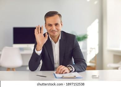 Happy smiling man in suit sitting at office desk, looking at camera and waving hand saying hello during video call. Webcam portrait of business coach, CEO, financial consultant or university professor
